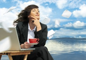 businesslady with laptop is working beside a lake.